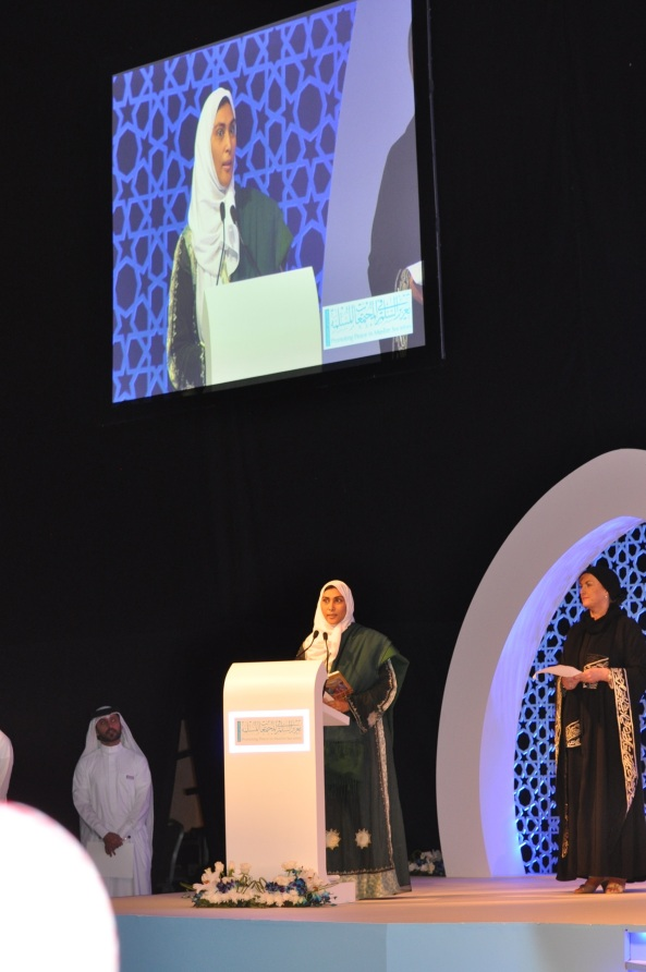 Nimah at Peace Forum Reading poem closing  wide shot with screen and Judge Marlyn- UK - Abu Dhabi  March 10 2014  cropped   1